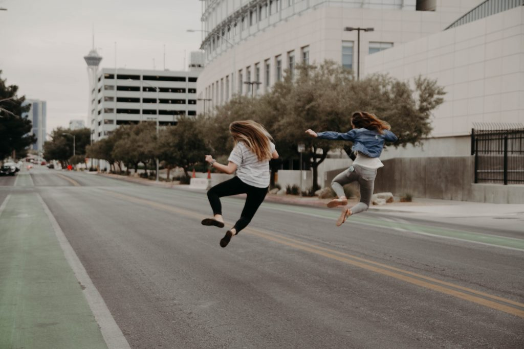 two woman jumping on the street during daytime looking happy