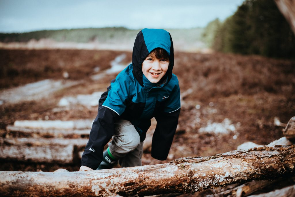 boy climbing on tree stump