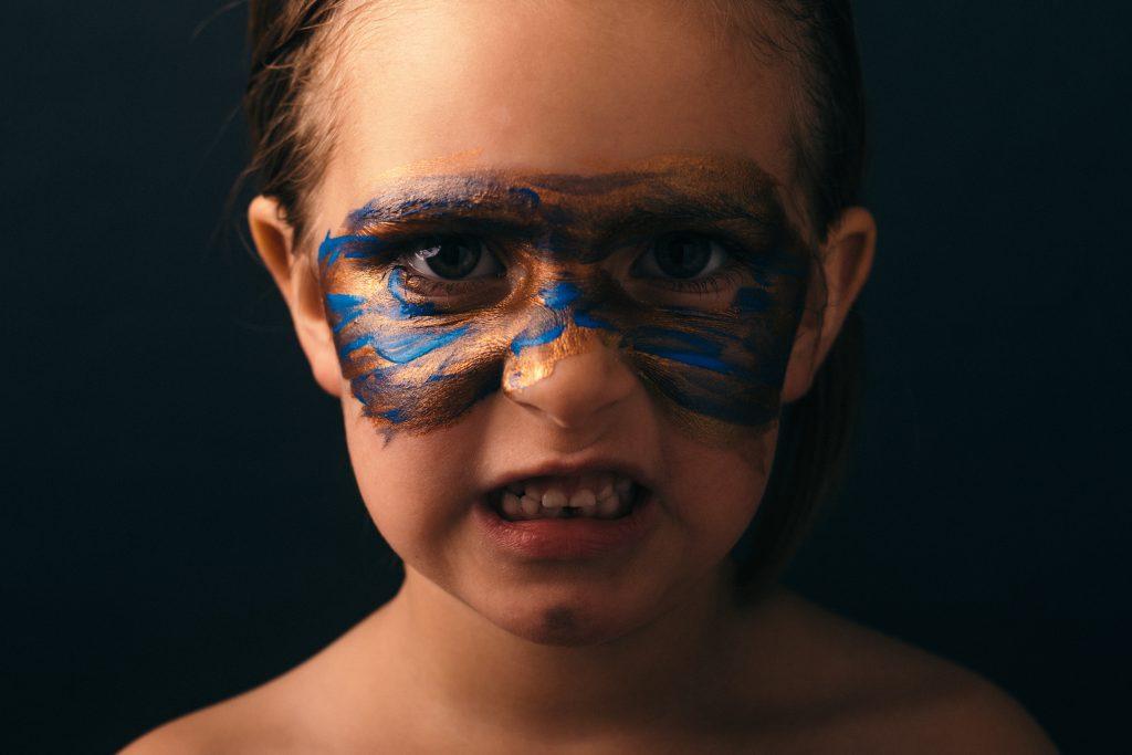 dziewczyna nosi portret farby twarzy wygląda zły