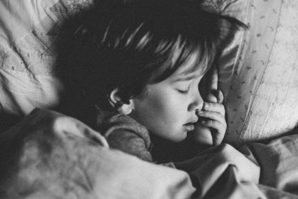 gray scale photo of girl sleeping on white pillow