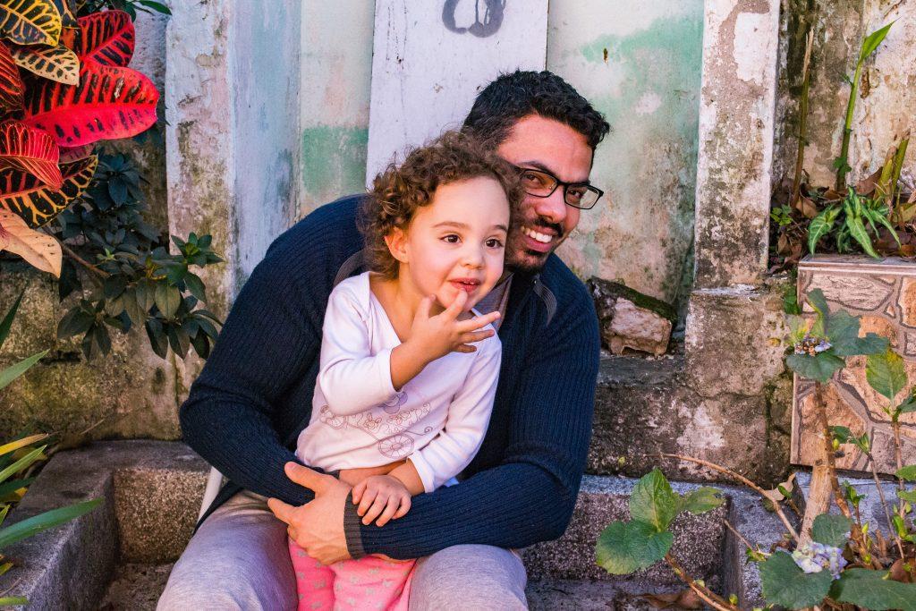 mężczyzna siedzi z dzieckiem dziewczyna, który wygląda na szczęśliwego