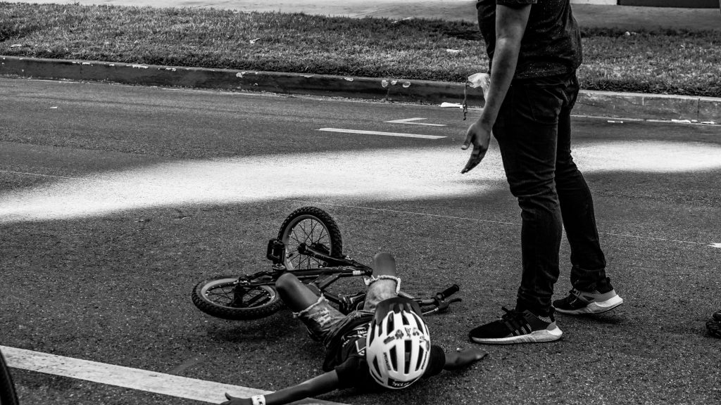 child lying on the ground beside bike and standing man