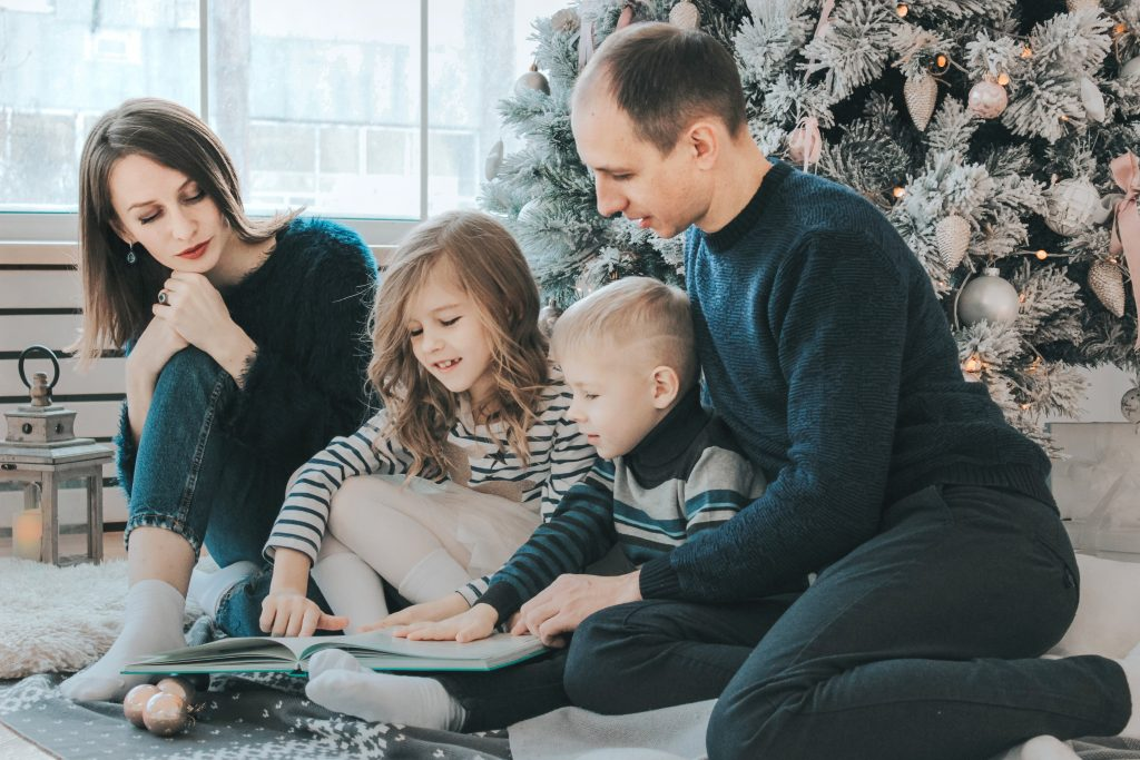 girl and boy child reading book sitting between father and mother beside Christmas tree family time