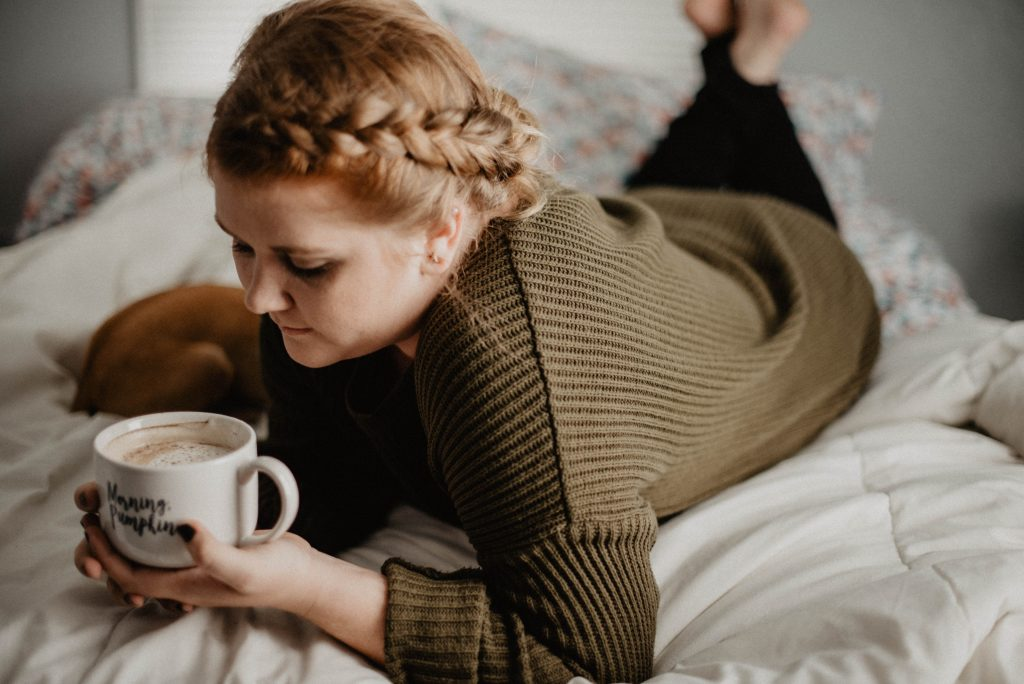 woman on bed holding white mug