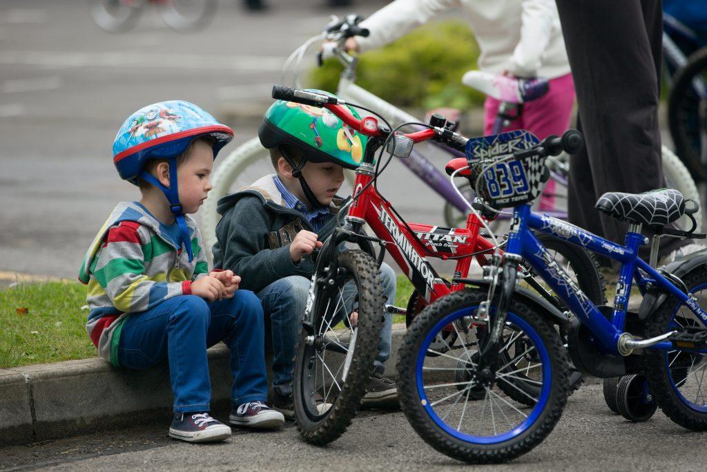 kids seating near bicycles near street