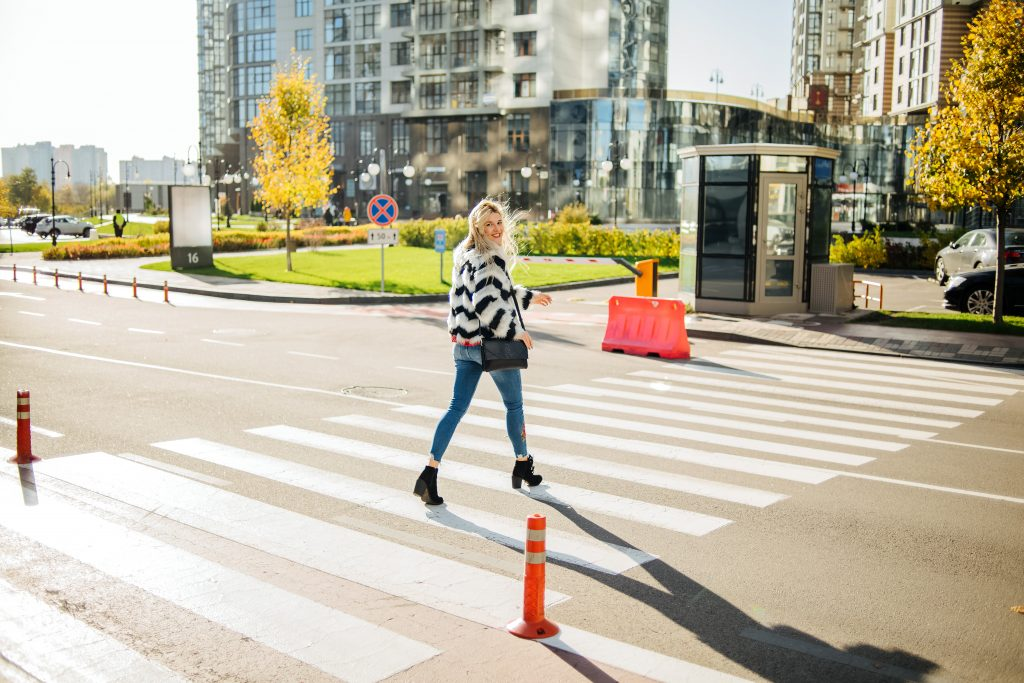 woman passing over zebra crossing on street